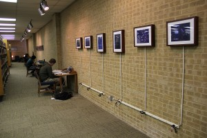 A student connects his laptop to one of three exhibition display areas in the J. Ardis Bell Library on NE Campus. Two areas downstairs and one area in main lobby will feature digital artwork submissions from students, faculty and staff. Photo by Zach Estrada/The Collegian