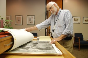 College archivist Tom Kellam looks through old maps of northern Tarrant County. These and other historical items on NE Campus chronicle the district's as well as the local community's history.       Photos by Taurence Williams/The Collegian