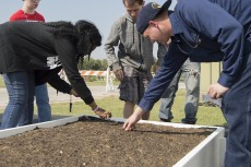 Marc Villanveva, right, assists students in planting the first seedlings of the new garden on SE Campus. Photo by Christina Feyisetan/The Collegian