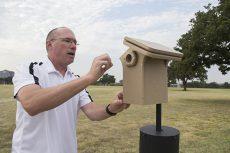 Bird enthusiast and kinesiology associate professor Tim Sebesta tends to a birdhouse.