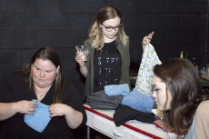 Nicole Sephard and Sarah Dirskill fold laundry while Morgan Mizell drinks during the one-act play Laundry and Bourbon.Photos by Bogdan Sierra Miranda/The Collegian