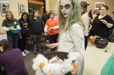Brittney Walker offers candy from her smoky spooky cauldron to incoming guests. Children could walk along the path and have candy dropped into their backpacks during the children's center Candy Walk. Photo by Christina Feyisetan/The Collegian