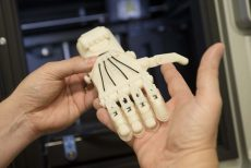Brooke Thompson holds a 3-D printed hand to show one of the many objects that can be printed with this new technology.