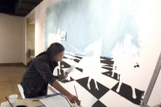 NW student Humna Raza paints her piece, What's Your Next Move? The art features human shapes fighting. Her message was about critical life choices.   Photos by Luis Hernandez Jr./The Collegian