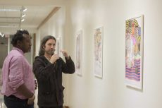 SE instructional assistant Christopher Blay and artist Adam Palmer review the exhibit.