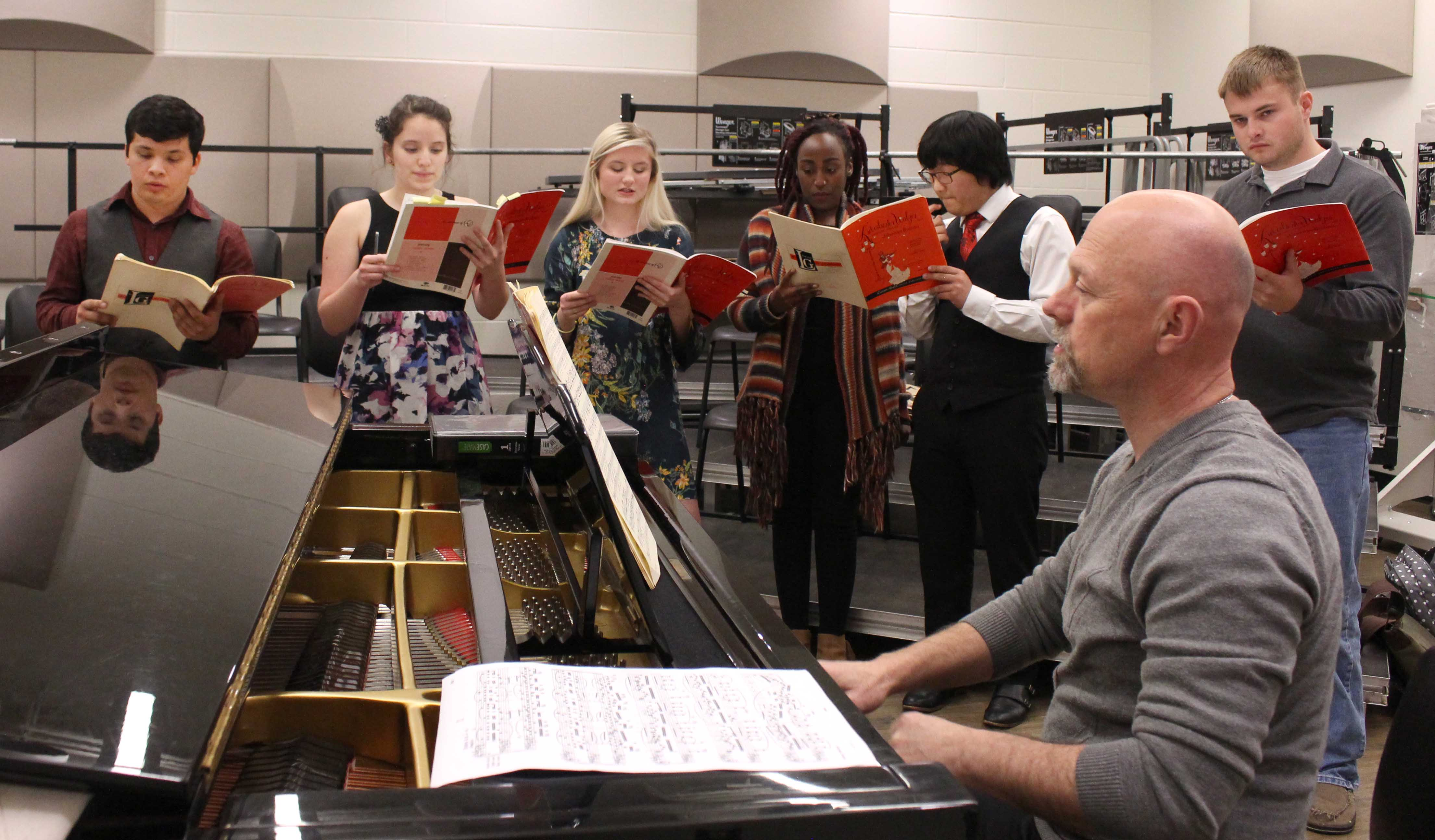 NE music instructor and choir director Stan Paschal works with students as they learn their parts for a song they will perform during the Dessert Theater.