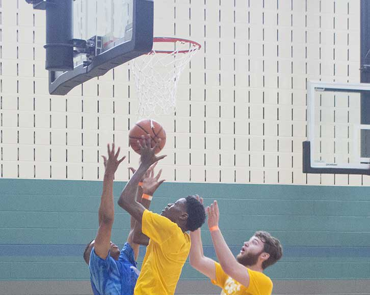 Clint Otwori jumps to make a basket. Otwori scored 23 points in the first game and helped lead his team to win the SE Campus basketball tournament.