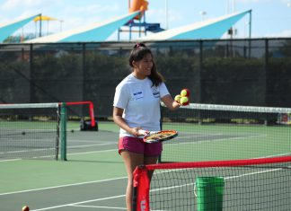 NE student Ingrid Pineda serves tennis balls for children to practice their backhand swing.