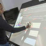 NE media services coordinator Cedric Hights demonstrates the moveable, interactive board that displays projected images that instructors can mark up using special tools to make classes more interactive.