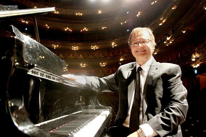 South music professor Oscar Dressler poses with the piano he performed on during a concert in Buenos Aires, Argentina.