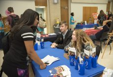 Cornerstone Honors program secretary Megan Taylor and social chair Brandon Ezell talk with student Carrie Walker about the program.