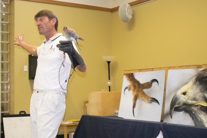 Blackland Prairie Raptor Center executive director Erich Neupert holds Orville the American kestrel at a lecture on SE Campus Sept. 5.
