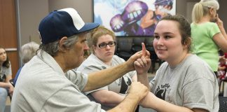 TR student Delaney Toone uses her hands to communicate with Glynn Shrods, a deaf and blind man from Fort Worth who shared his story with Deaf, Deaf World attendees.