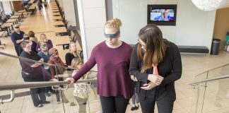 Natalie Brown guides Shelby Stokman on the stairs at TR as the Sign Language Interpreting Program Practicum I class spent Oct. 3 learning to navigate challenges on campus.