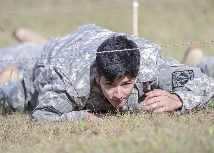 Polytechnic High School student Sebastian Barrera, a member of the U.S. Army JROTC, crawls under wires during the American GRIT obstacle course competition Nov. 9 on TR.