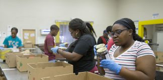 South students Latricia Douglas and Jasmine Carey help package and sort food items Nov. 17 to be delivered to food pantries around Tarrant County. They volunteered through the Students Targeting and Reaching Success program.