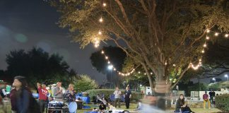 NE students Sihanya Rocha and Mayra Aguilera sit on a blanket and enjoy the atmosphere of the Harmony event Nov. 15, which included live music and lights strung from the trees.
