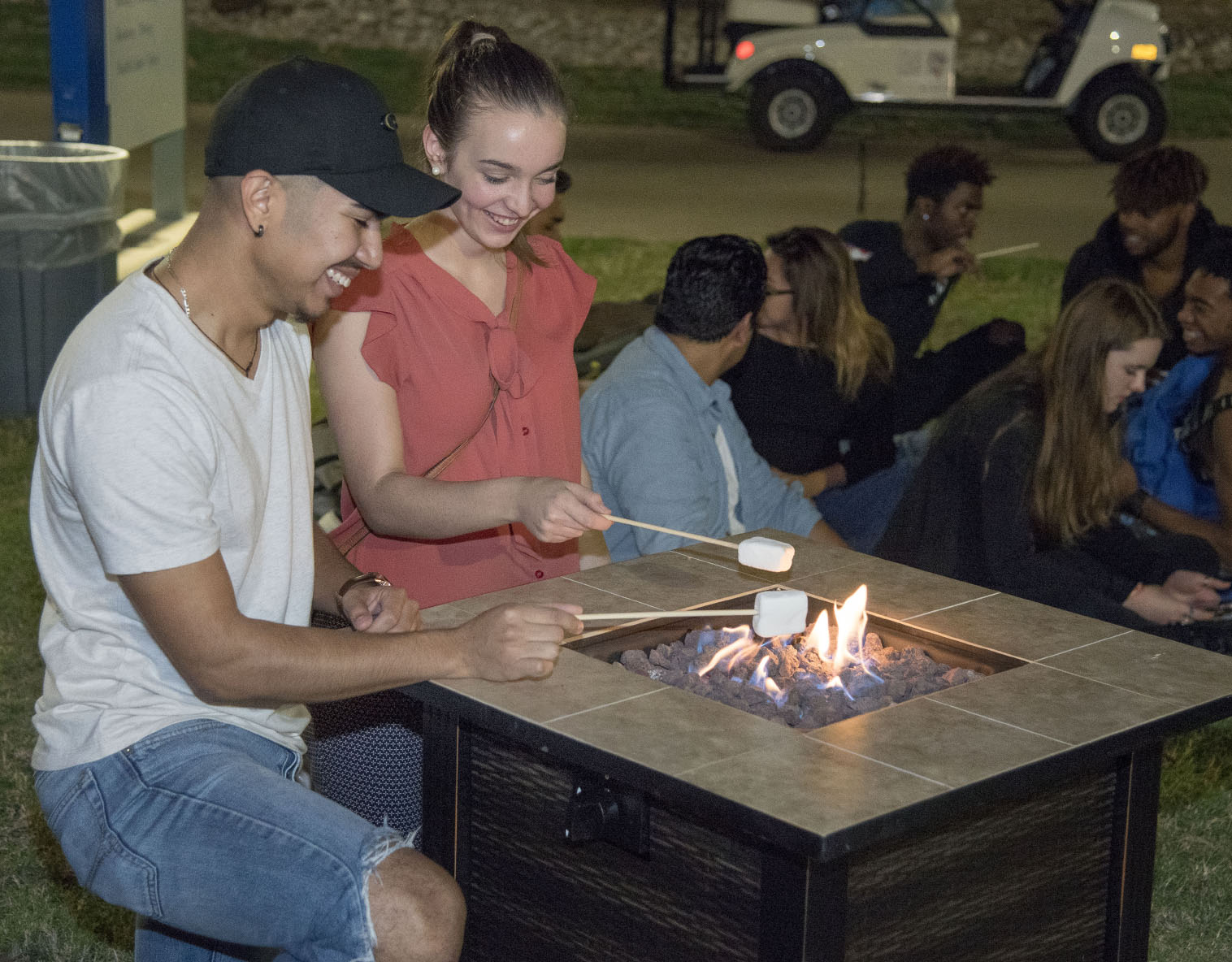 NE students Ramon Gasca and Bridget Faricy roast marshmallows to make s'mores at firepits located around the event on Nov. 15 on NE Campus.