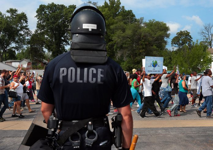 A police officer watches as protesters march in front of the Ferguson, Missouri, police station in August 2014. Law enforcement's treatment of minorities has continued to be a nationwide issue ever since.