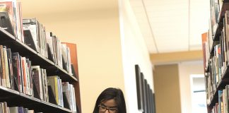TR work-study student Tatiana Flores skims a book during her library shift.