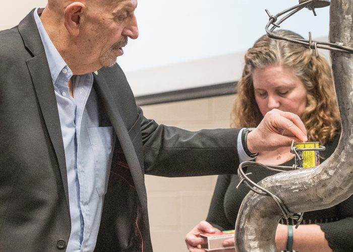 Holocaust survivor and speaker Paul Kessler lights a candle during a short prayer service at the beginning of the memorial Jan. 25 to commemorate International Holocaust Remembrance Day on South Campus.