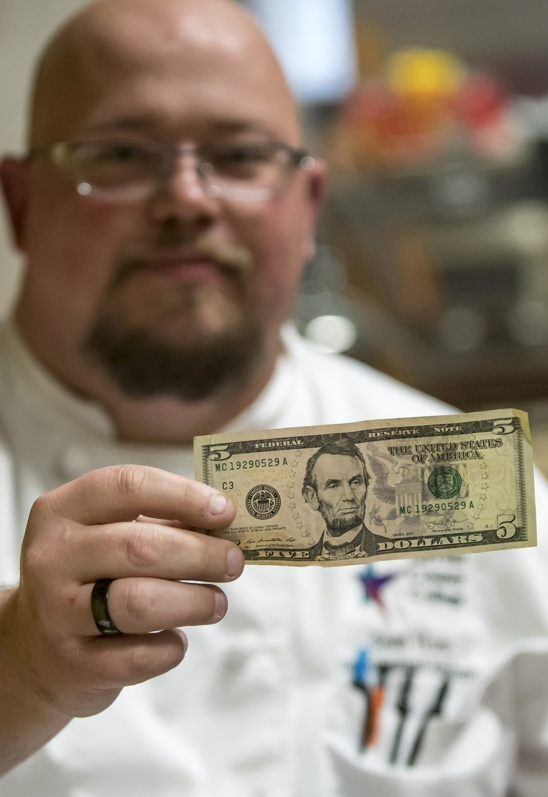 SE culinary arts instructional assistant Sean Hunt holds a $5 bill, which will buy a lunch prepared by the program.