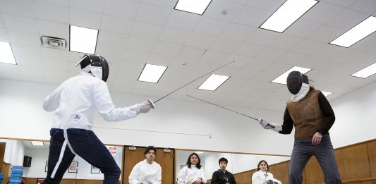 South early college high school student Julio Aguero practices one on one with Vinnie Bradford as other fencing club members observe Feb. 7.