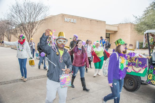 Students passed out goodies and blew noisemakers as they celebrated Fat Tuesday in traditional Mardi Gras masks and costumes for the parade Feb. 13.