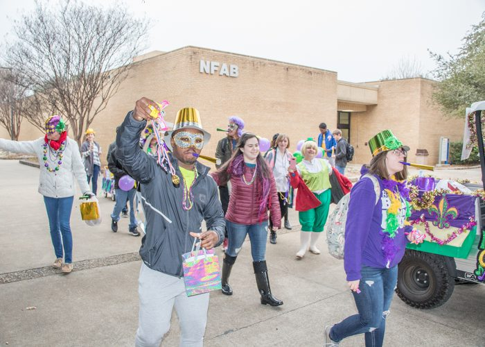Photos by Suzann Clay/The Collegian Students passed out goodies and blew noisemakers as they celebrated Fat Tuesday in traditional Mardi Gras masks and costumes for the parade Feb. 13.