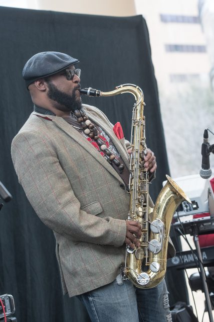 Sylvester Jones belts out notes on the sax while performing on TR.