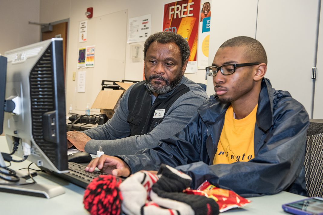 SE coding instructor Joe Charles sits with student Jordan Carter as he works. This class is offered through the campus' Community & Industry Education office.