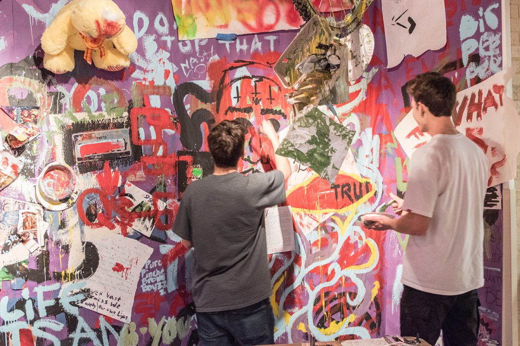 NW students Quinton Bailey and Spencer Alexander add to the collective art mural during the art-centered weeklong event in the Lakeview Gallery.