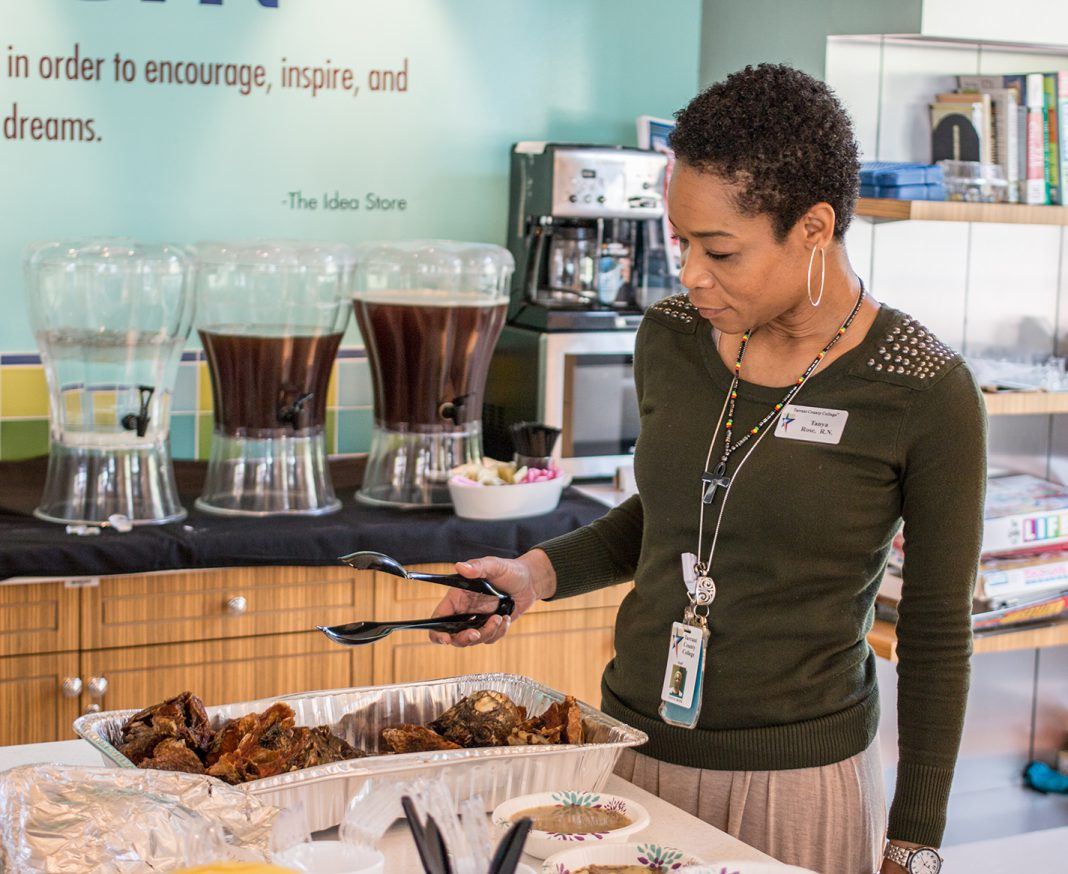 TR nursing assistant professor Tanya Rose picks up fried fish brought to the Multicultural Potluck Lunch in TR's Idea Store April 4. Students, faculty and staff were encouraged to bring dishes from their culture.