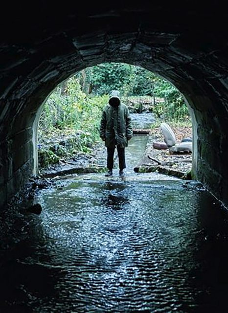 A mysterious figure eerily stands at the end of a tunnel, which is one of many creepy, atmospheric moments in the British horror film Ghost Stories.