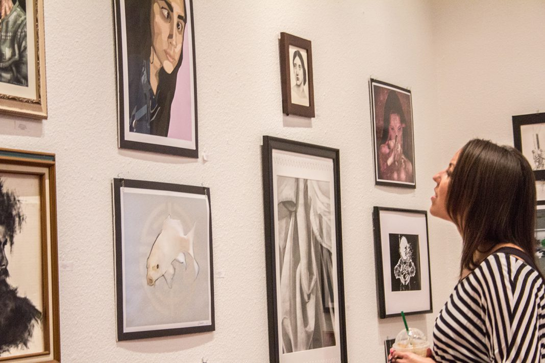 South student Nicole Harris looks at works during the closing reception of the Student Art Show April 26 in the SPAC Carillon gallery on South Campus.