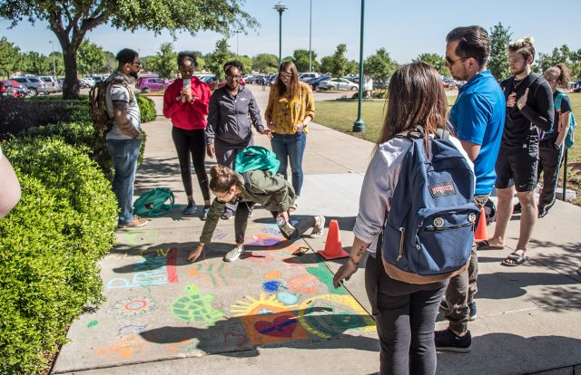 SE students work on a group psychology of personality project. Students chalked designs on the walkway between the ESEE and ESED wings on SE Campus.