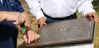 South facilities manager Gus Anderson and carpenter Gary Turnbull open the campus' 20-year-old time capsule April 19.
