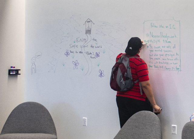 SE student Sam Carrillo writes on a dry erase wall in the learning commons.