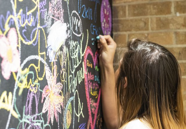 NE student Mindy Bounheuangvulay draws on the art department's graffiti chalkboard Aug. 24. The wall is a place for students to express themselves visually through their art and connect with fellow artists, said NE art associate professor Martha Gordon.