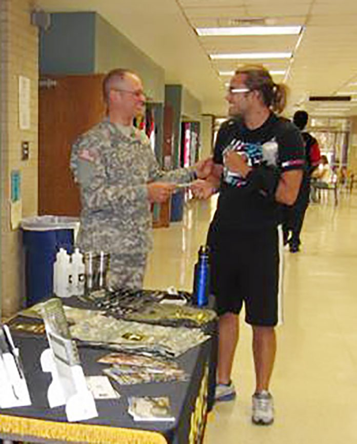 A recruiter offers a student information about military careers at a previous fair.