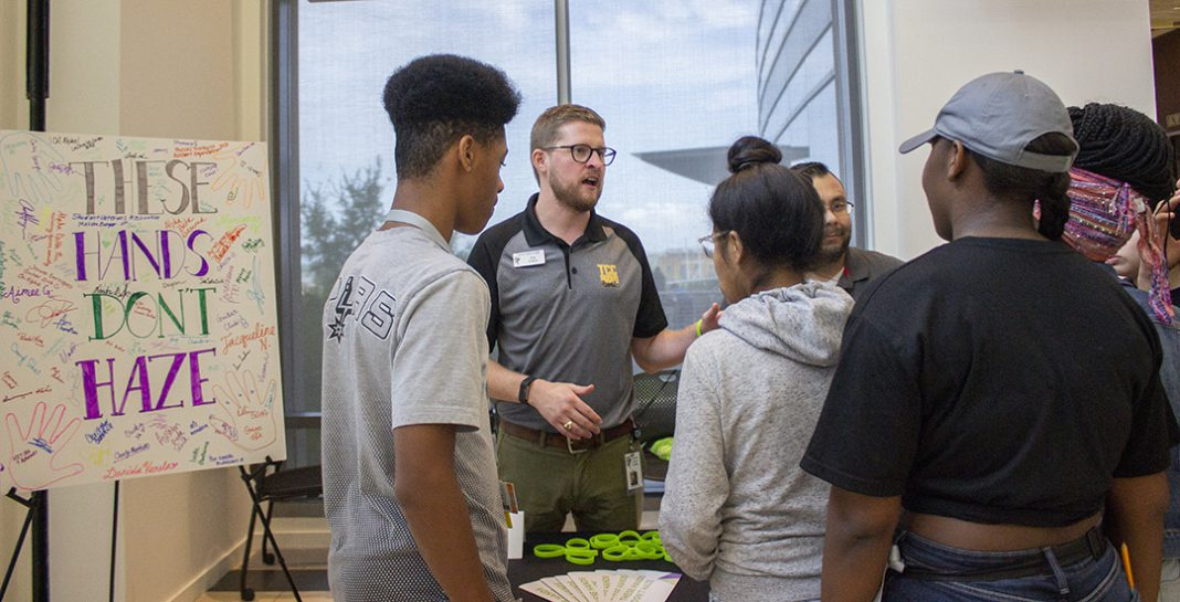 TR student support coordinator Tim Cason discusses the consequences of campus hazing with TR students at the These Hands Don't Haze table set up on TR's Main Street during the campus' Club Crawl Sept. 6.