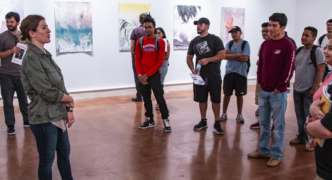 Visual manager Melissa Stoner discusses the prints on display with students during the opening reception for the exhibit Aug. 30 on South Campus.