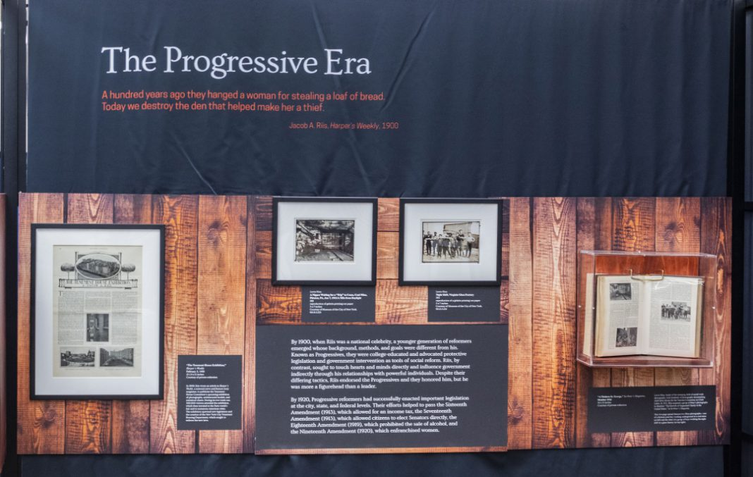 The display shows Jacob Riis influence through literary work with a younger generation of reformers in the 1900s called The Progressives whose impact shaped American history.