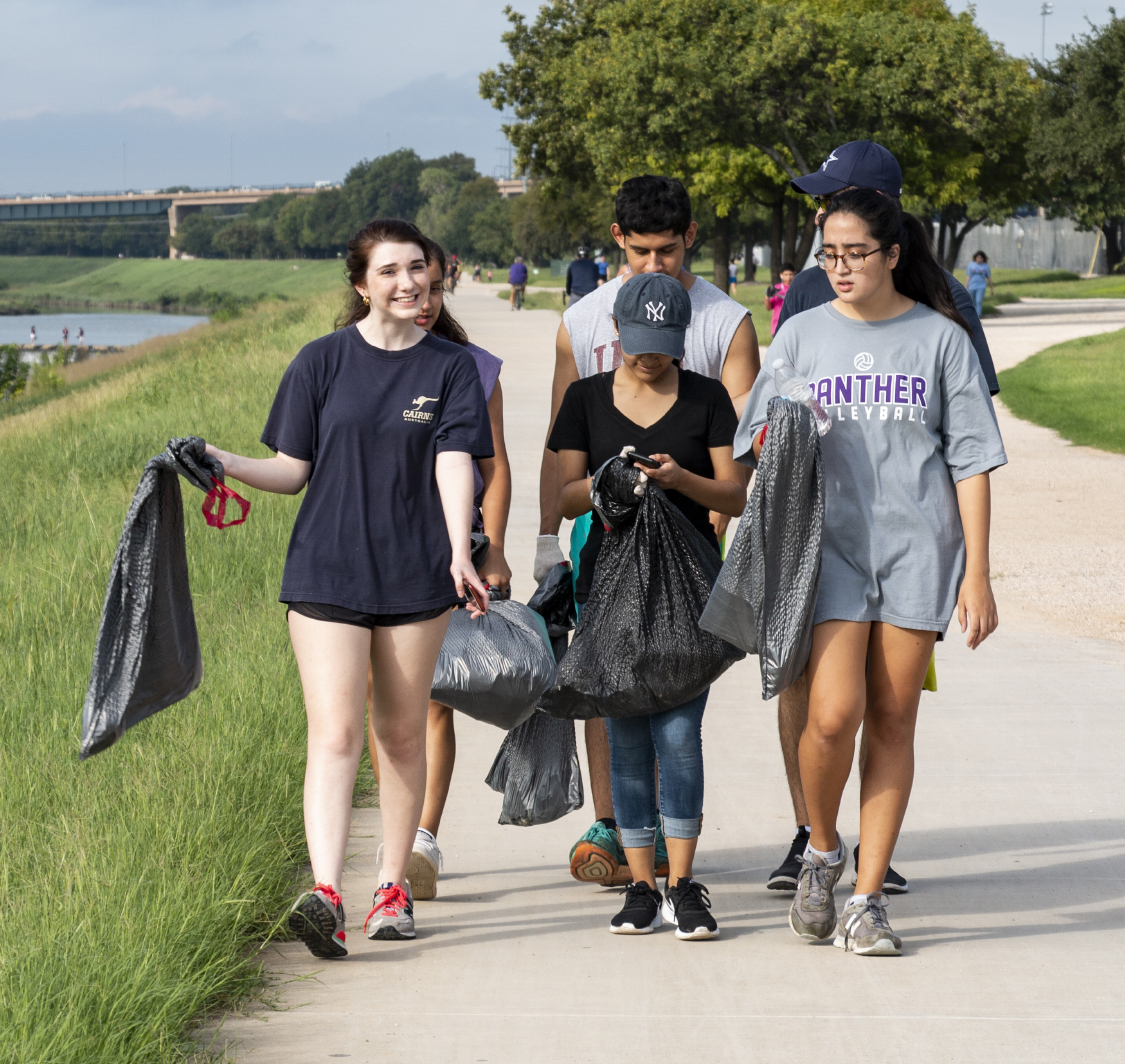 Trinity Trash Bash participants travel along the path next to the Trinity River to clean up bottles, cans and plastic bags along the riverbanks on Sept. 15.