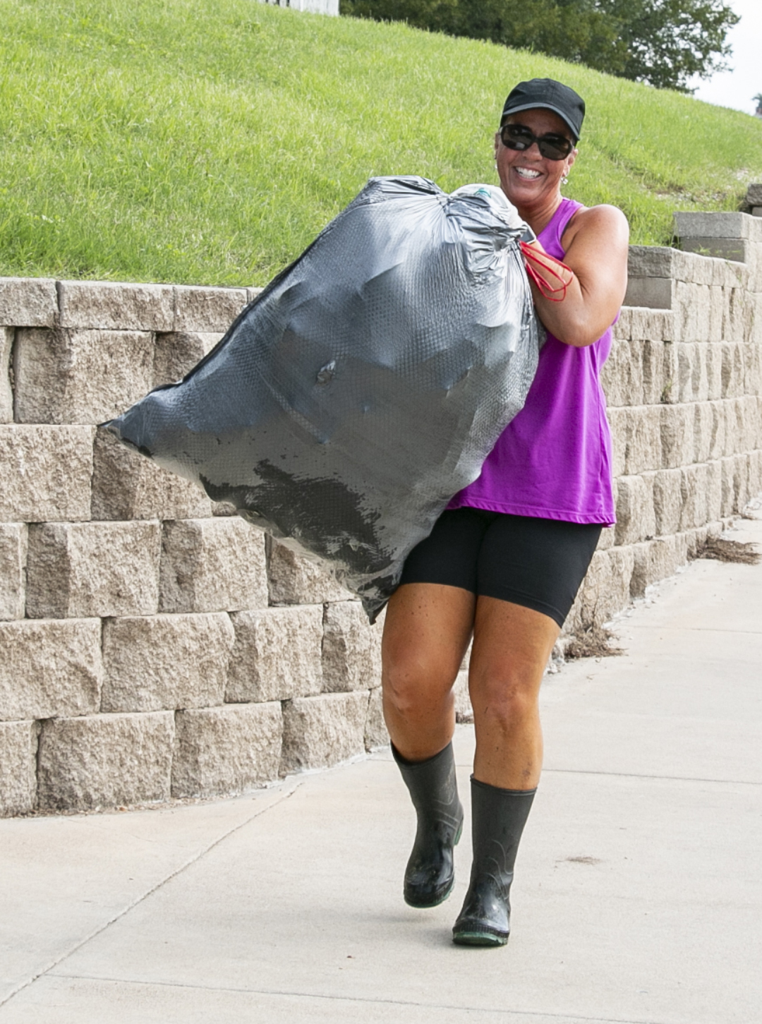A Trash Bash attendee heads toward the starting area with a filled garbage bag. Trash bags and gloves were provided.
