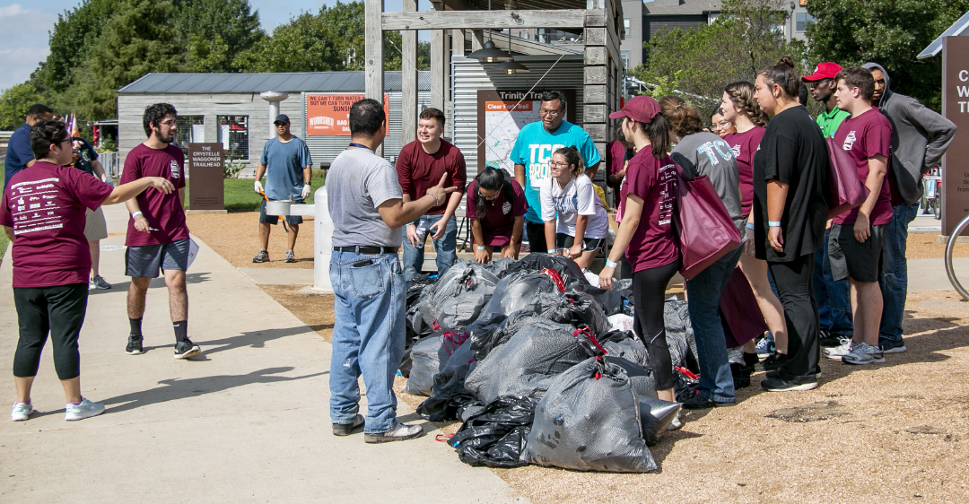Attendees drop off their filled garbage bags with trash collected from riverbanks during the Trinity Trash Bash on Sept. 15. Forty-seven TCC students made it out to the event and were joined by other community members and organizations.