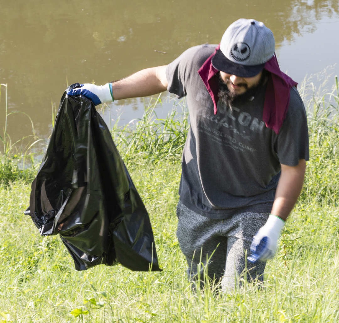 A Trash Bash participant searches for garbage on the banks of the Trinity River. TCC students and other community organizations gathered Sept. 15 to clean up the river.