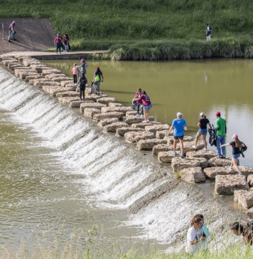 TCC students and other community members walk along the rocks across the Trinity River in Fort Worth to pick up trash during the Trinity Trash Bash on Sept. 15. Garbage and gloves were provided to all participants.