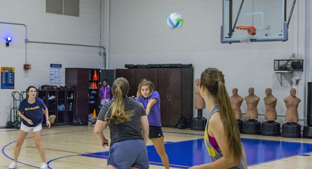 NW student Caitlynn Gonzalez plays the ball as her teammates look on. Around 20 students showed up to participate in intramural volleyball on NW.