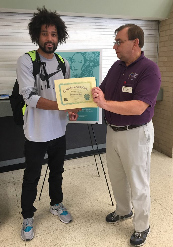 NW student Shelby Jones receives a certificate of completion from NW computer science instructor Paul Koester for successfully completing Level 3 in 2017's Candy and Coding.